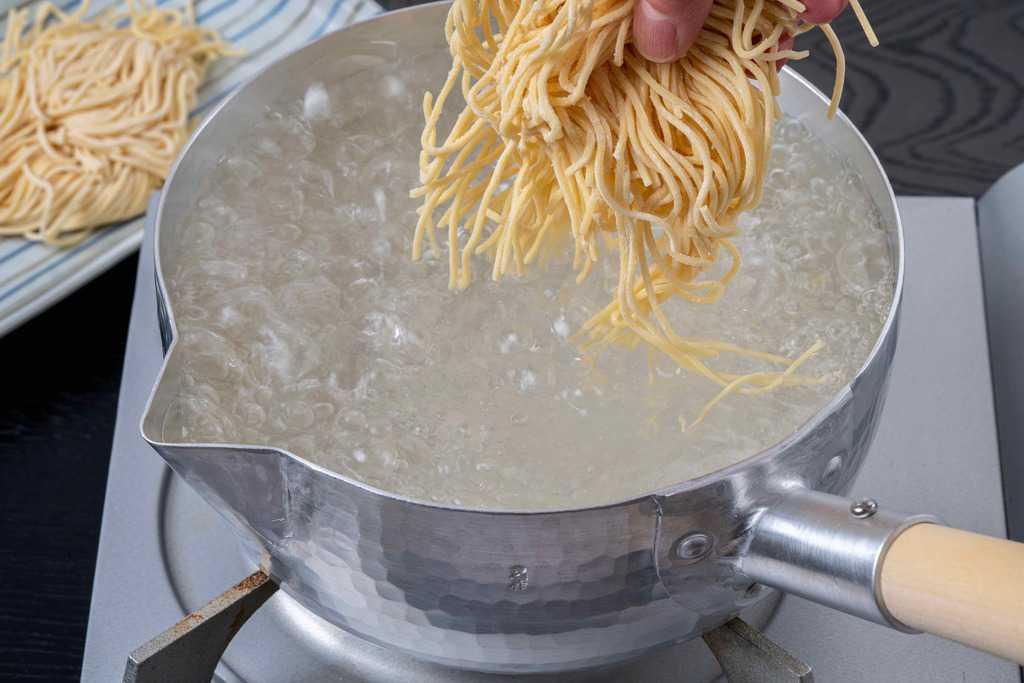 熱湯で熊本ラーメンの中太ストレート麺を茹でる、熱湯にラーメンの麺を投入する