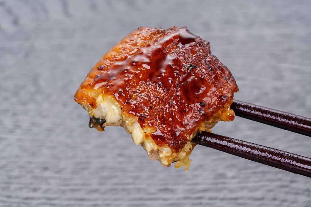 くら寿司のお取り寄せウナギの蒲焼き一切れを箸でつまむ