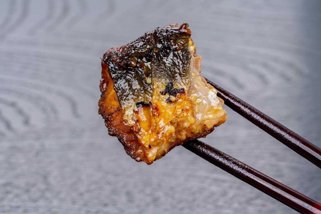 くら寿司の通販うなぎ蒲焼の一切れを箸でつまむ、皮の焼き加減を見せる