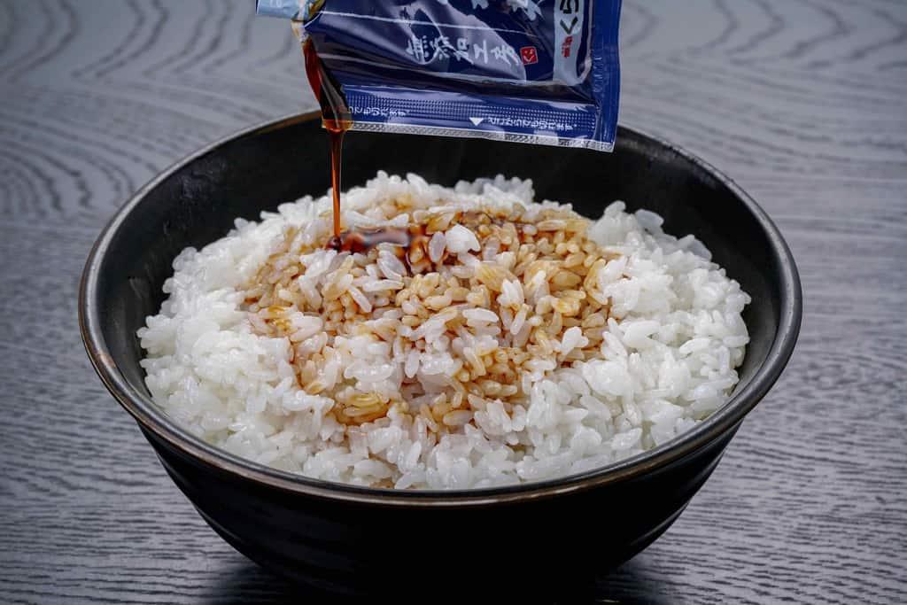 丼に入った白飯にくら寿司のうなぎ蒲焼のたれをかける