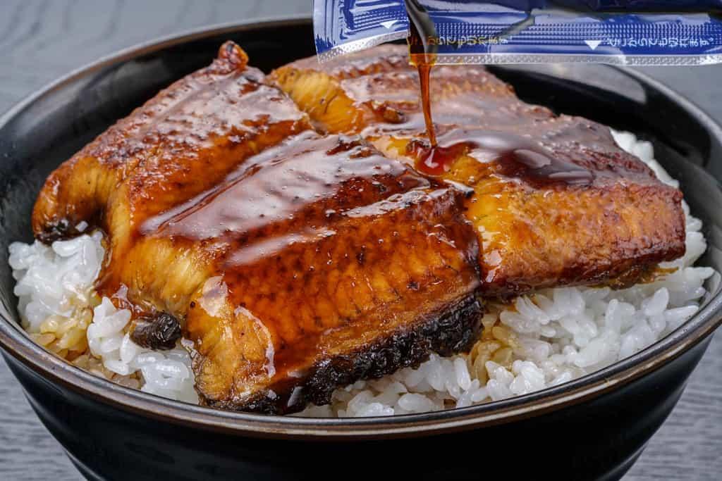 丼ご飯の上のくら寿司のうなぎ蒲焼に蒲焼きのたれをかける、うな丼、うな重