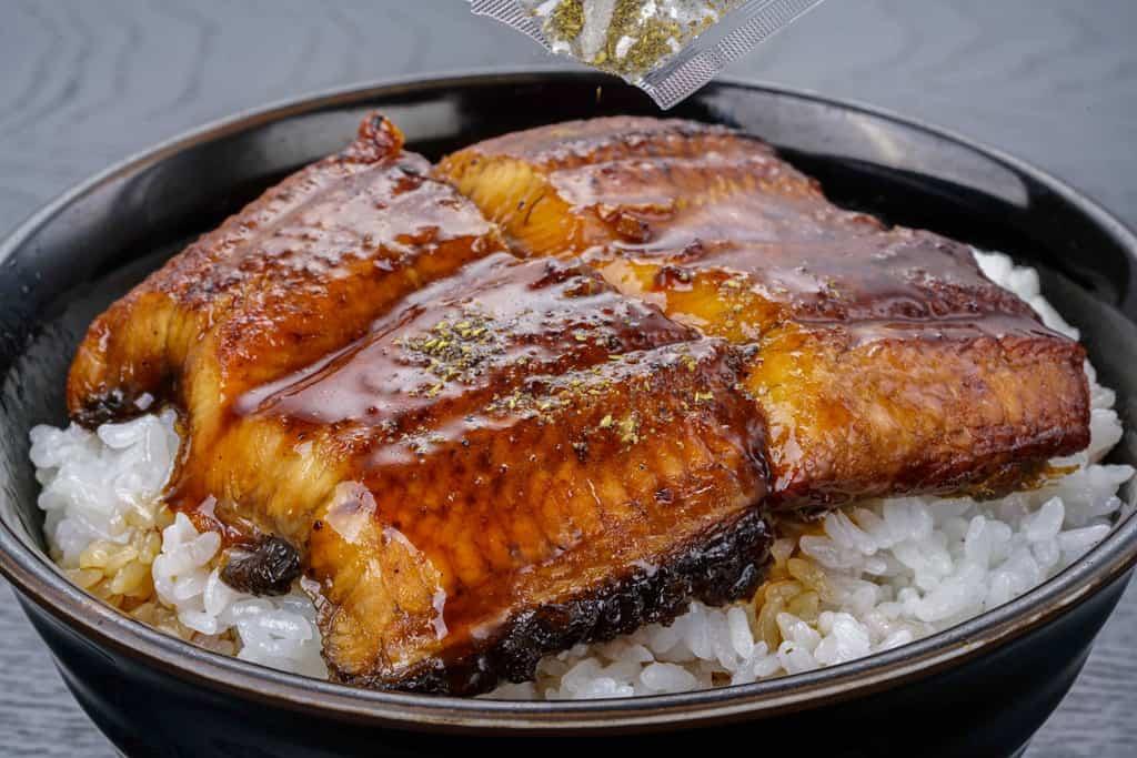 うな丼、うな重、くら寿司のうなぎ蒲焼に山椒を振りかける