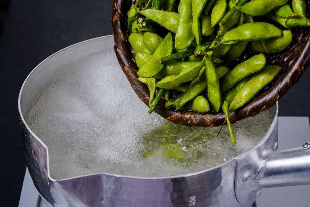 沸騰したお湯が入った雪平鍋にはねっ娘会の枝豆を入れる、茹で枝豆