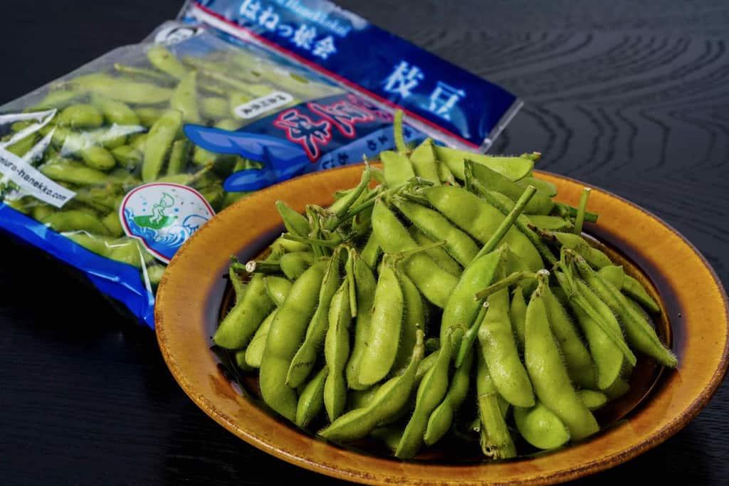 皿の上の「はねっ娘会の枝豆」300gと袋に入った枝豆