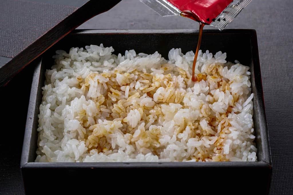 重箱に入ったご飯にうなぎの蒲焼きのたれをかける