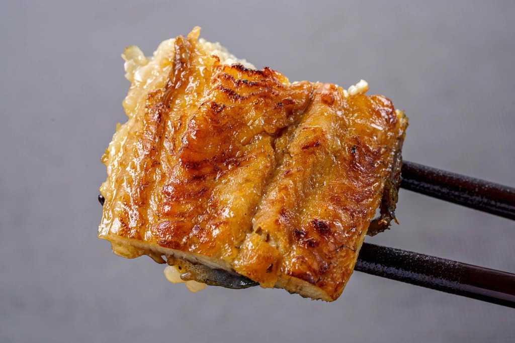 浜名湖山吹のうなぎ蒲焼きを箸で持つ、ふっくらとしたうなぎの蒲焼き
