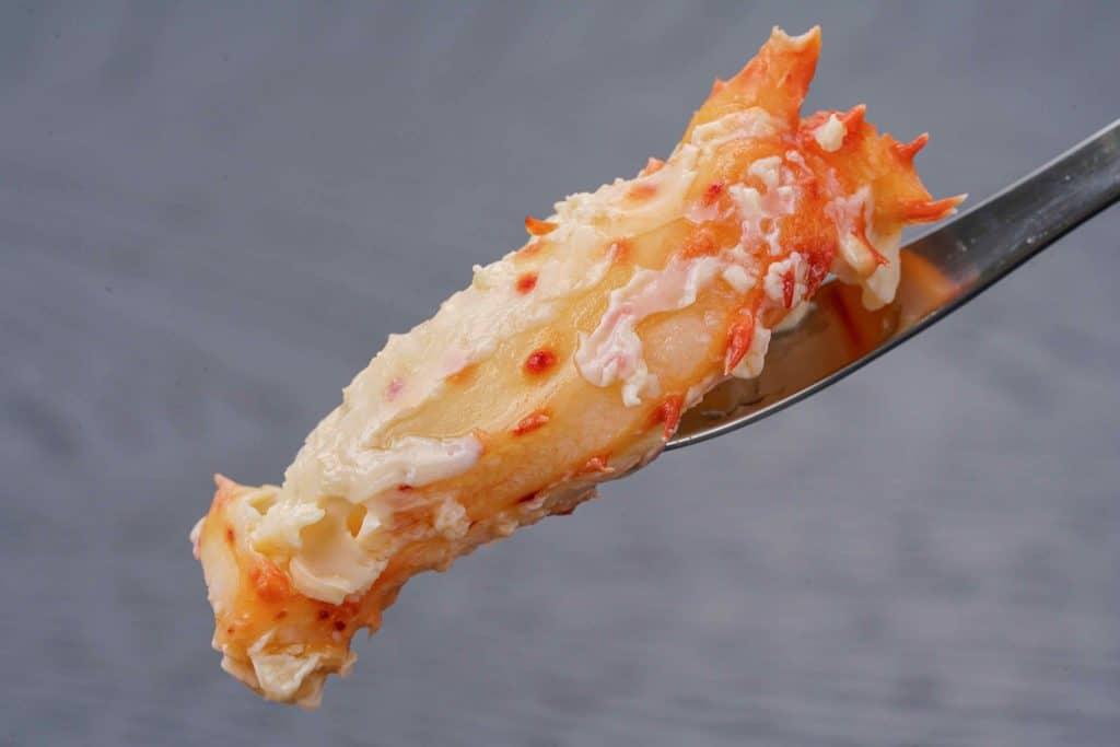 カニフォークで花咲ガニの身を持ち上げる、蟹フォークに刺した花咲がにの脚肉
