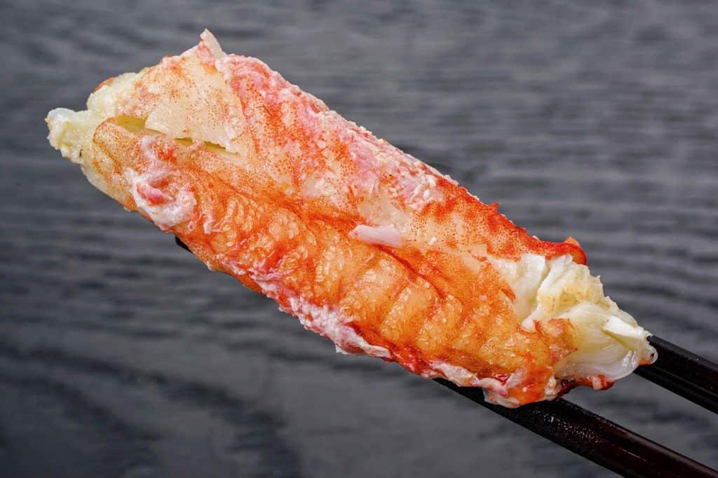 ロシア産ボイル毛蟹の身を箸で持つ、超特大ジャンボ毛蟹の脚肉
