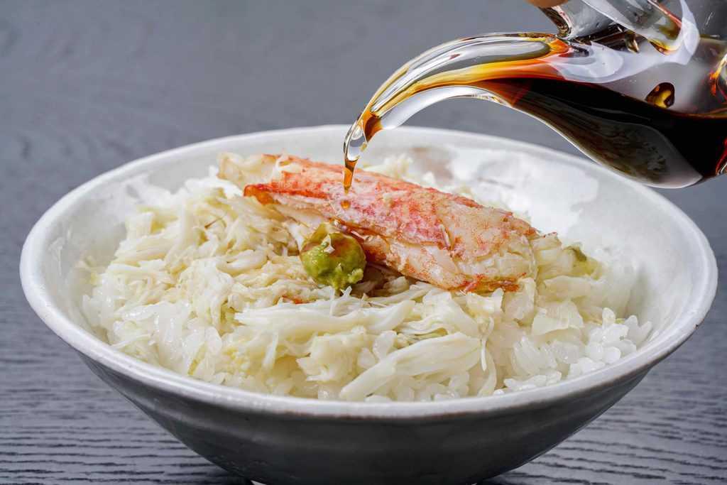 毛蟹の肩肉と脚肉を白いご飯に乗せて醤油をかける、毛蟹ご飯