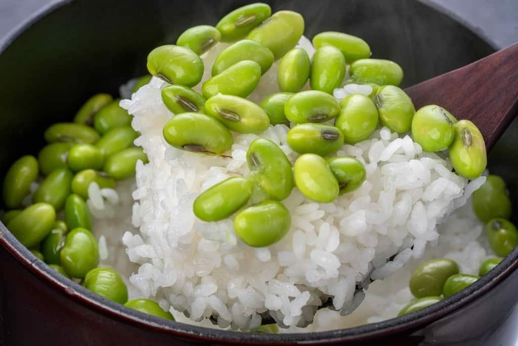 炊きたての毛豆枝豆ご飯をしゃもじですくう、いたや毛豆のご飯