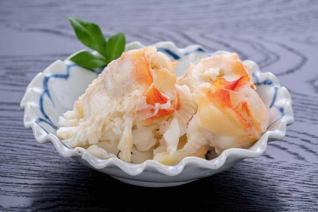ロシア産ボイルタラバガニの肩肉を皿に盛り付ける、