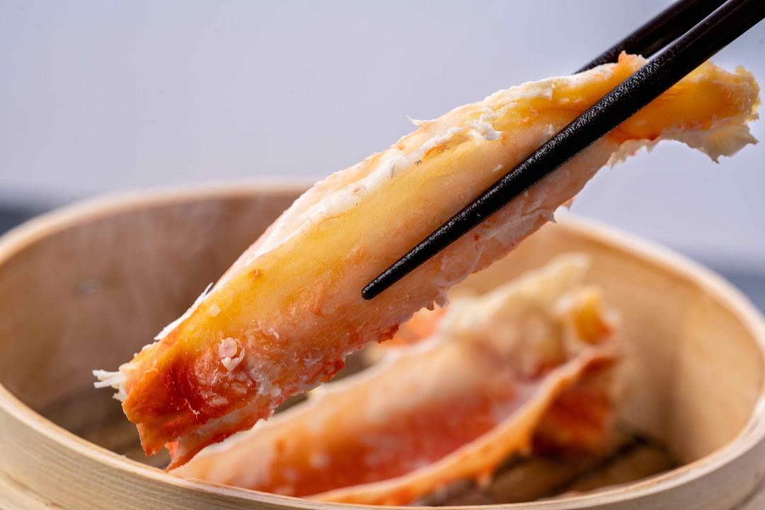 蒸しタラバガニを箸で持つ